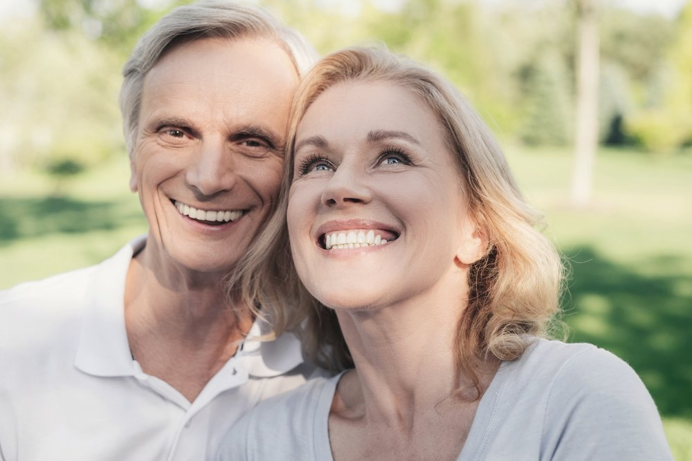 Older couple smiling after receiving dental implant treatment