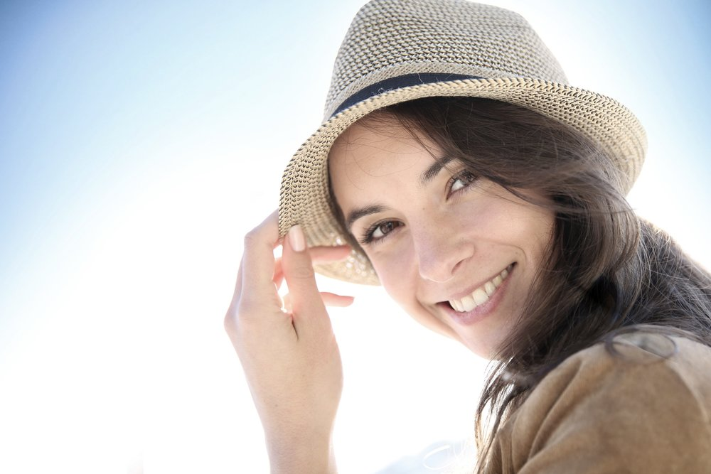 Pretty lady wearing a straw hat and a beautiful smile after having Cfast braces