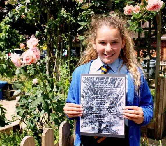 Rebecca Farnfield holding her winning poem