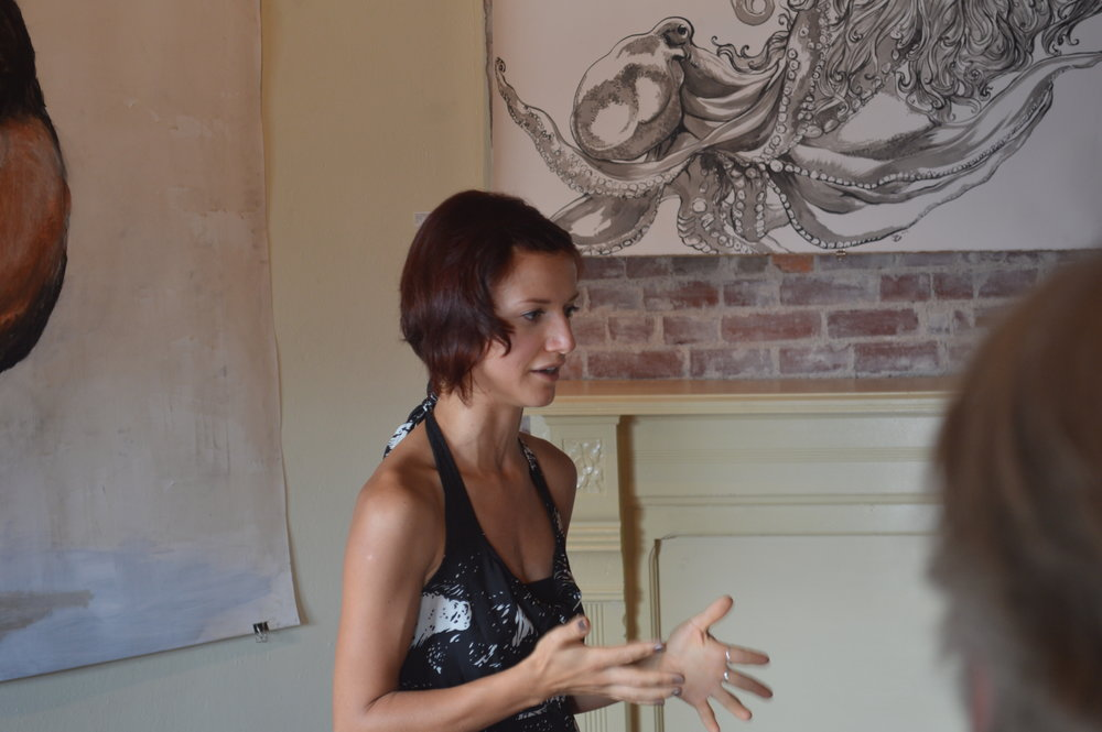 Still of the artist giving a talk on the work.