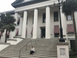 Jen Ross sits on the steps of Florida's State Capitol building in Tallahassee, FL