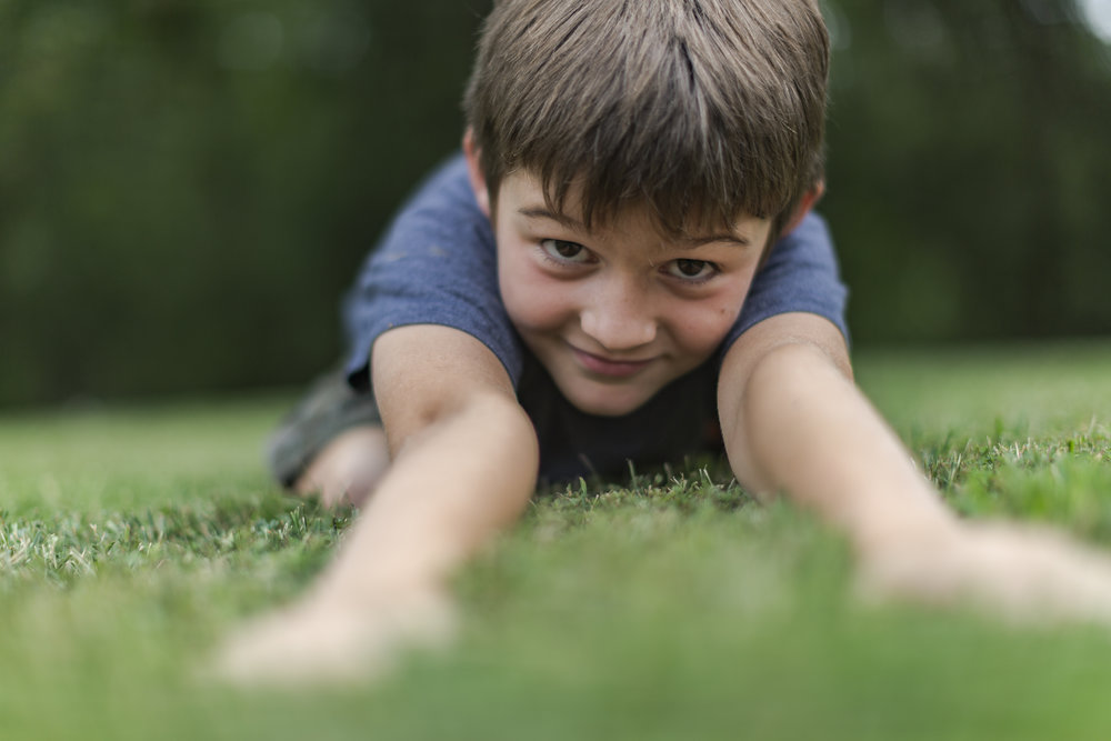 little boy stretches out on the grass of camp kumbayah