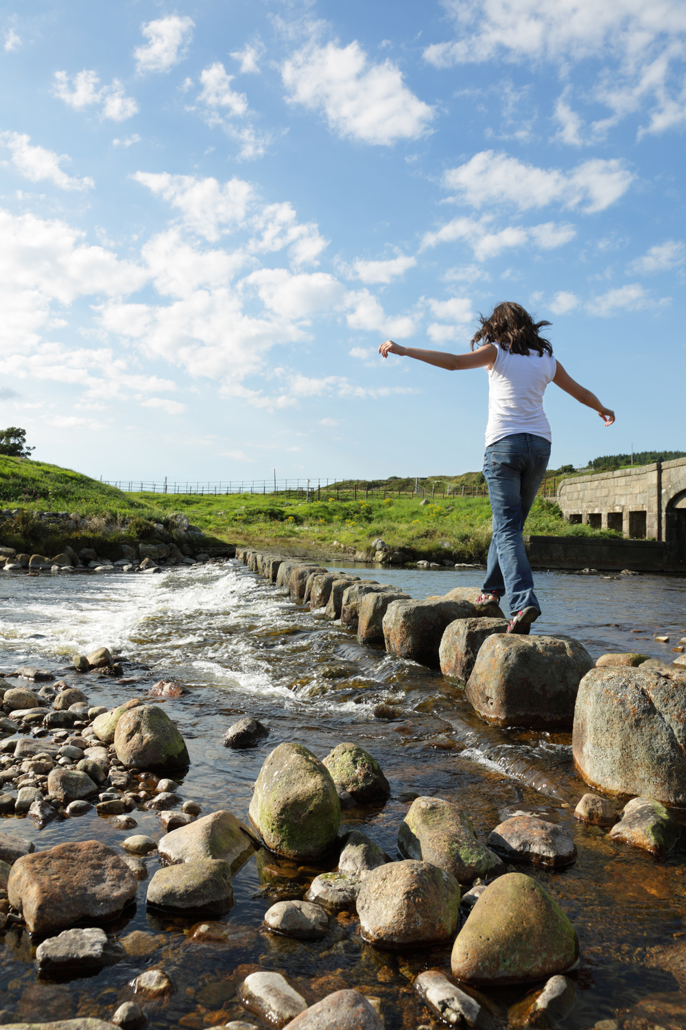 woman-crossing-river-on-rocks.jpg