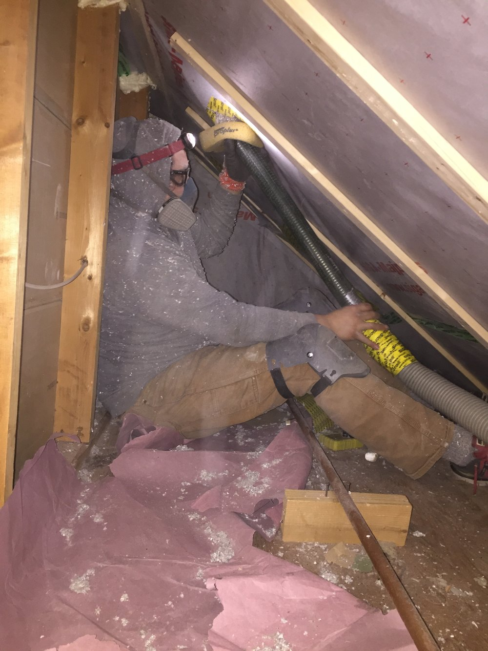 Luke dense-packing a kneel wall with cellulose insulation. -