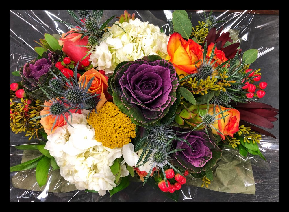 Floral arrangements with roses, hydrangeas, hypericum berries and kale at Russo's!