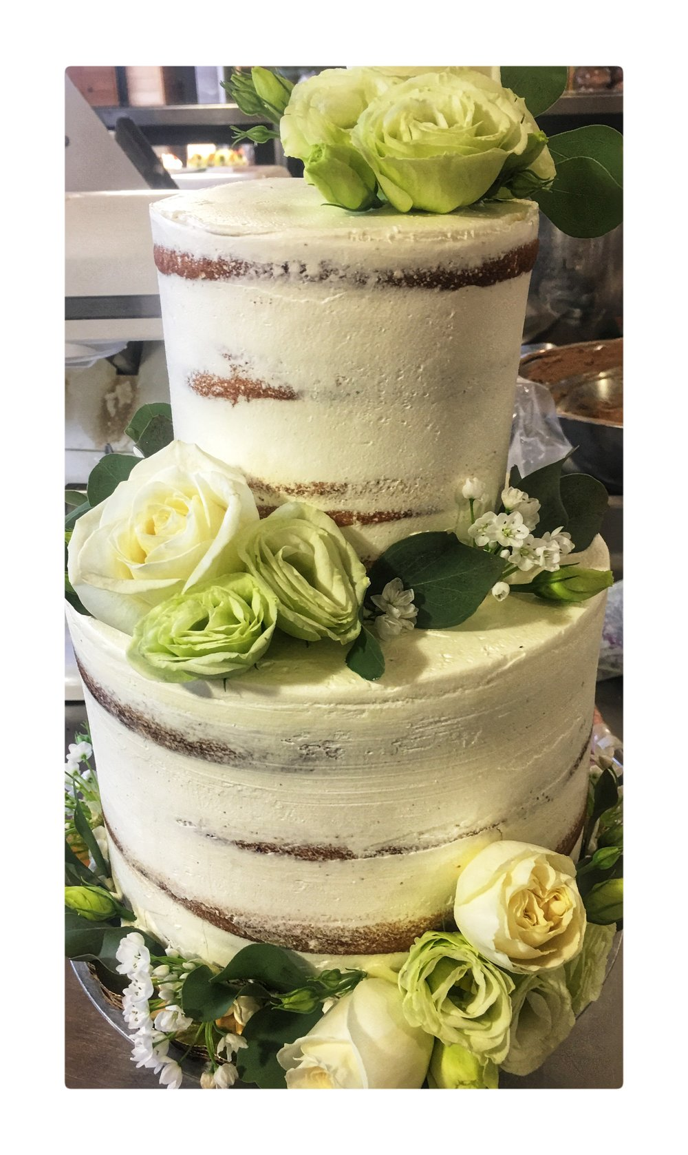 Cake decorated with fresh flowers and distressed frosting.
