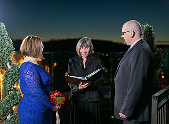 Mary officiates a nighttime rooftop wedding at Hotel Alex Johnson