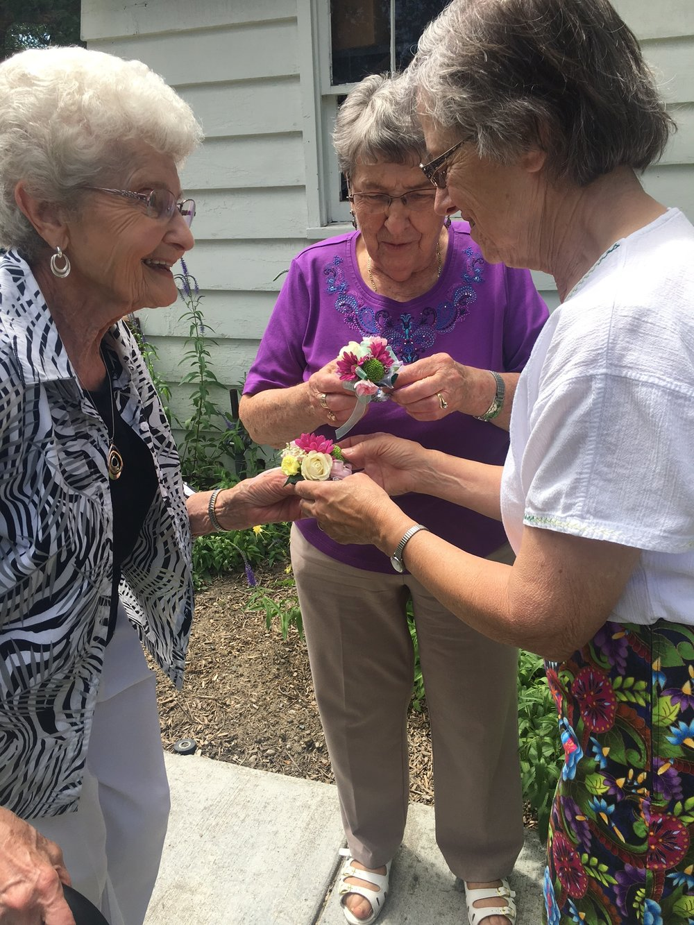 Sister Mary presents corsages to Cecelia Jirges and Irene Wolf in honor of their 20 years of volunteerism with Angela's Piazza.