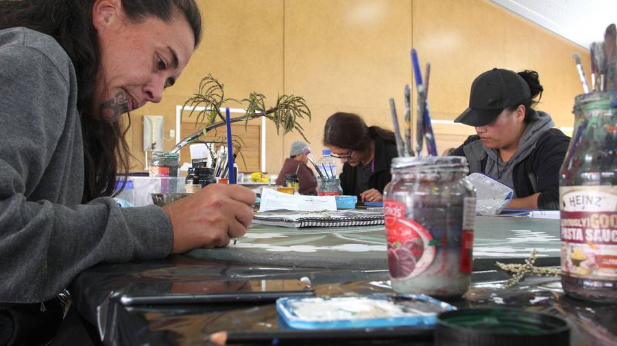 Art students (from left) Heni-Jane Puna-Whatarau, of Hastings, Ani Heperi, of Hastings, and Gemma Kara, of Napier, work on murals for the Pukemokimoki Marae celebrations. Photo/Duncan Brown