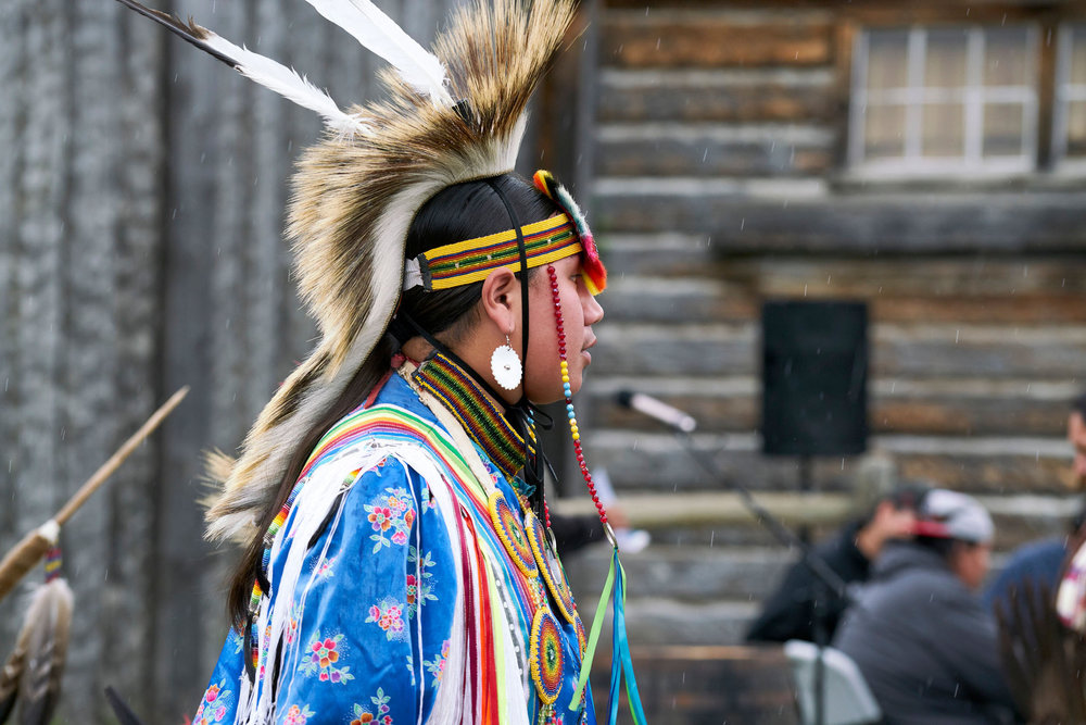 A Blackfoot dancer in traditional dress performing at an event at Fort Whoop-Up.