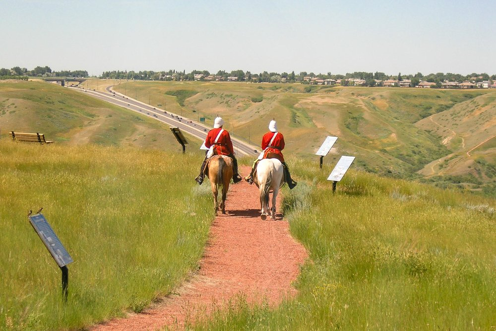 A pair of horse riders dressed in the red coats and white helmets of the early Royal Canadian Mounted Police riding on the trails near the Galt Museum & Archives.