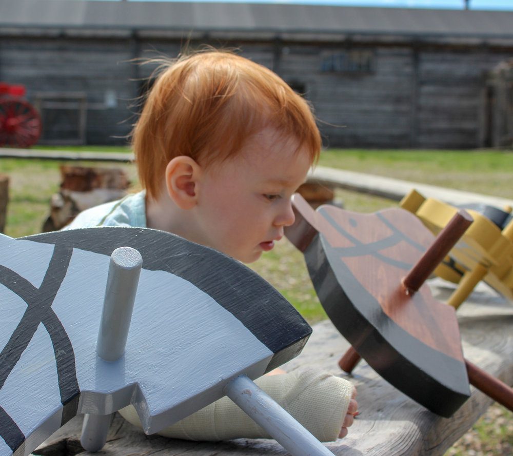 A child inspects the hobby horses in the Fort's compound.