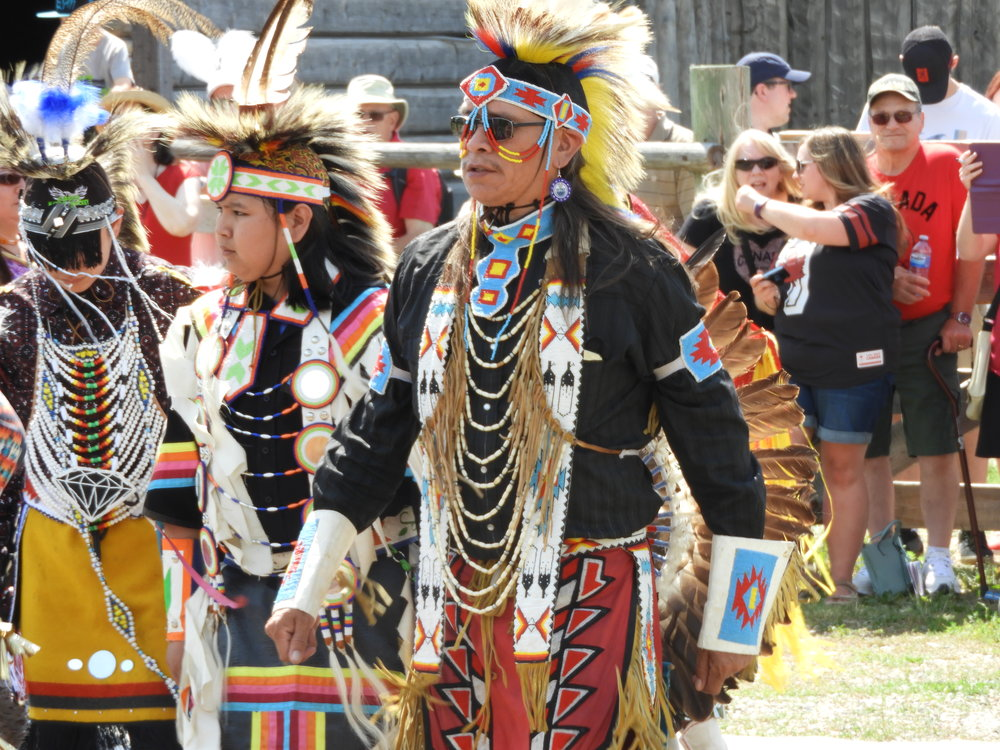 Photos of participants in regalia at a mini pow wow at Fort Whoop-Up