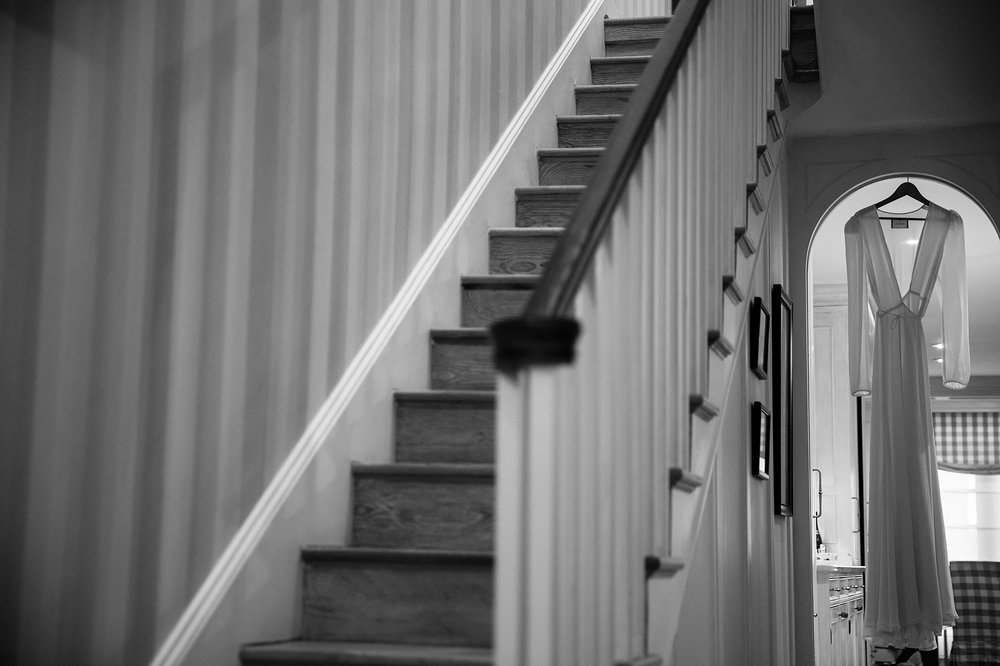 Wedding dress hanging in a hallway next to stairs