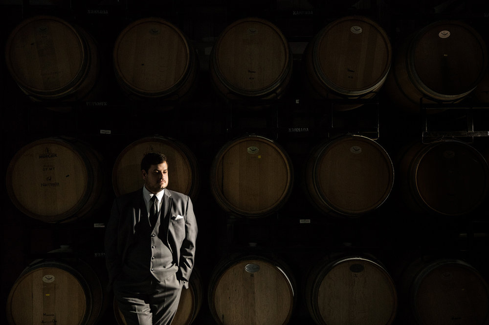 Groom posing in front of wine barrels at Narmada Winery before his wedding day