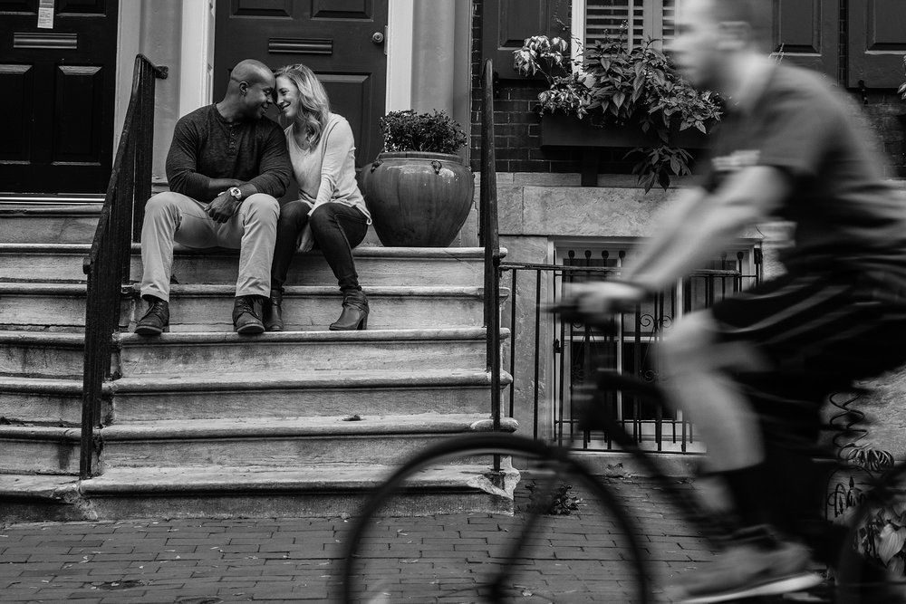 Couple sitting on front steps as a bicyclist rides by