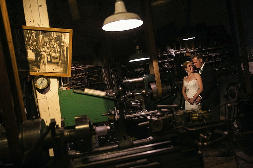 Bride and groom posing in a machine shop in the Baltimore Museum of Industry
