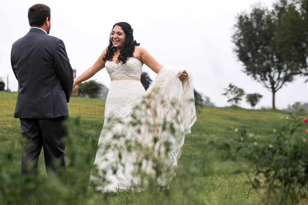 Bride and groom excited to see themselves during their first look on their wedding day in a field at a Virginia winery