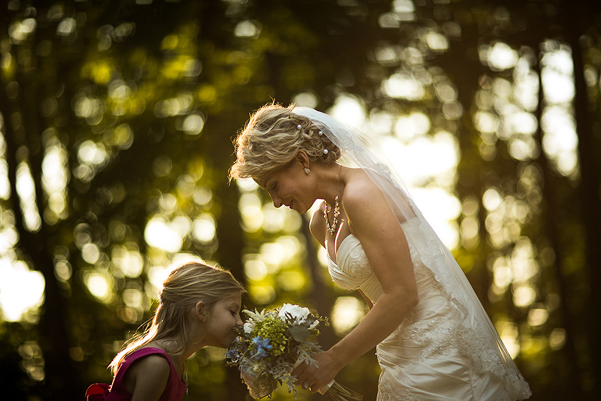 Little girl smelling a wedding bouquet held by bride outside at sunset