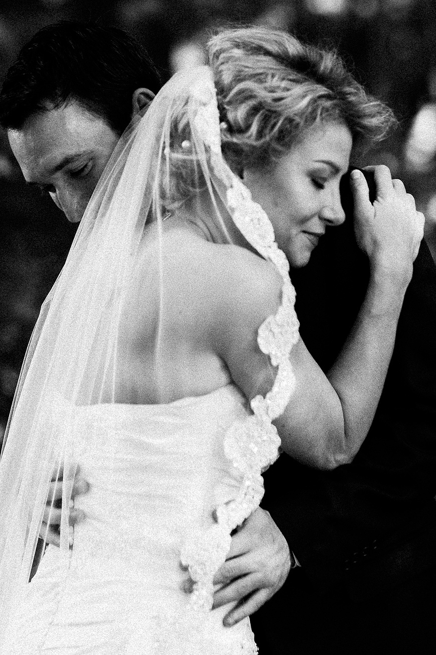 Bride and groom embrace during a touching moment, in black and white