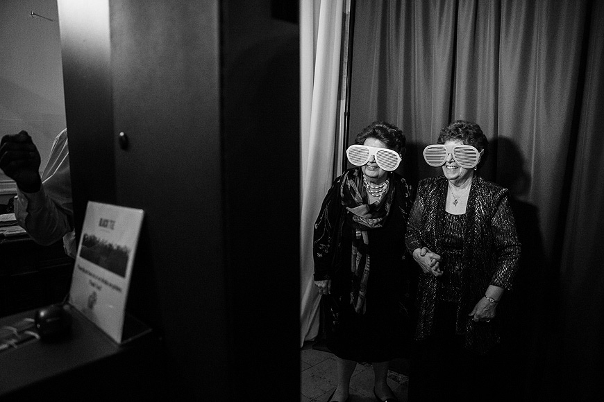 Wedding guests in a photo booth wearing funny oversized glasses