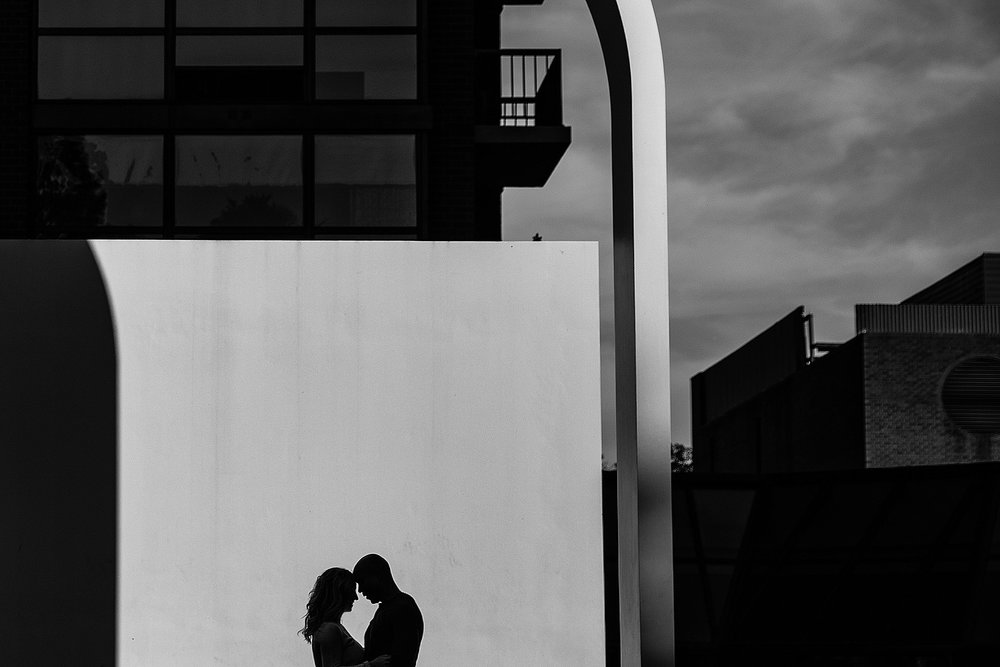 Couple silhouetted in front of a concrete wall with interesting shadows and curves