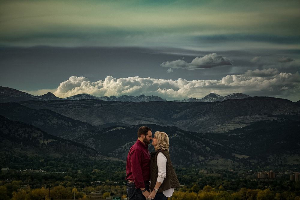 Couple posing in front of distant mountains and clouds in Colorado
