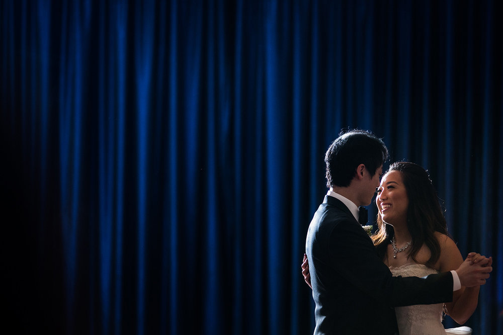 First dance between bride and groom in front of blue curtain at Virginia wedding