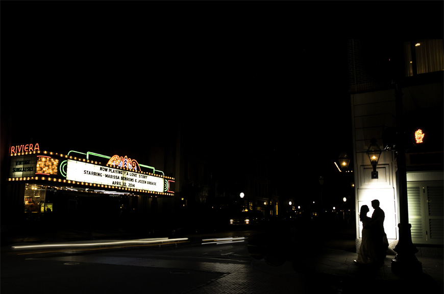 Bride and groom on their wedding day silhouetted in front of the historic Riviera Theater in downtown Charleston South Carolina