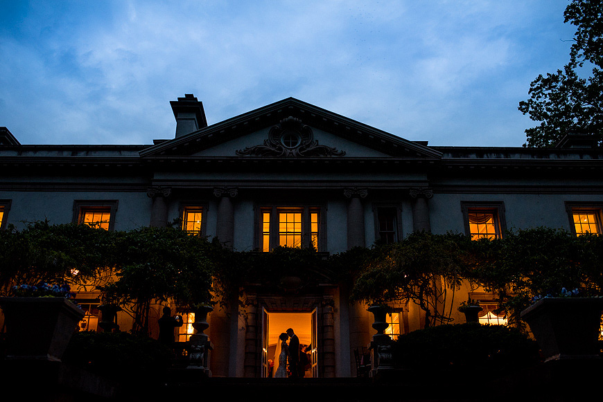 Wedding couple silhouetted in the front entrance of the Liriodendum Mansion