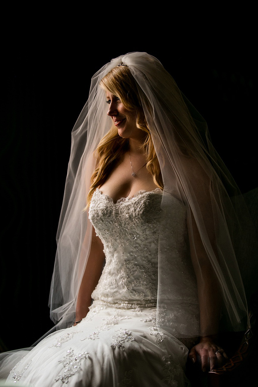 Bride posing in natural light against a black background on her wedding day in Baltimore, Maryland