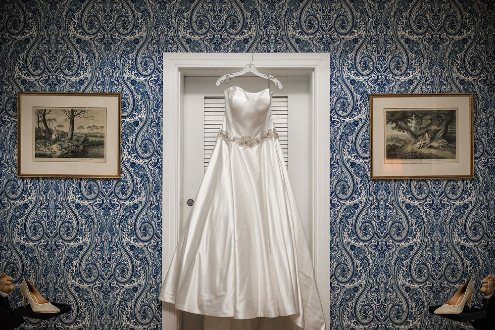 Wedding dress hanging in a doorway against a wall of blue paisley wallpaper