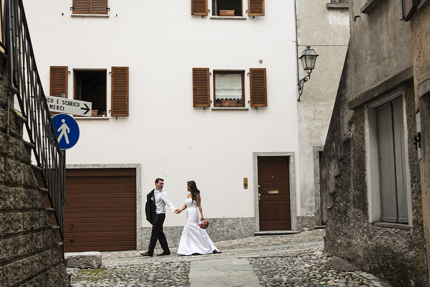 Bride and groom walking along a cobblestone street during wedding in Lake Como Italy