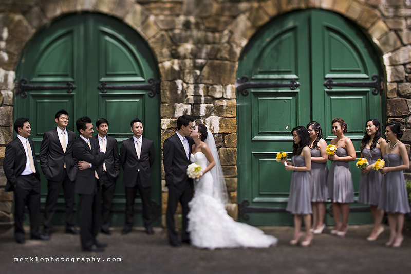 Bride, groom, and wedding party posing in front of green stable doors at Strong Mansion
