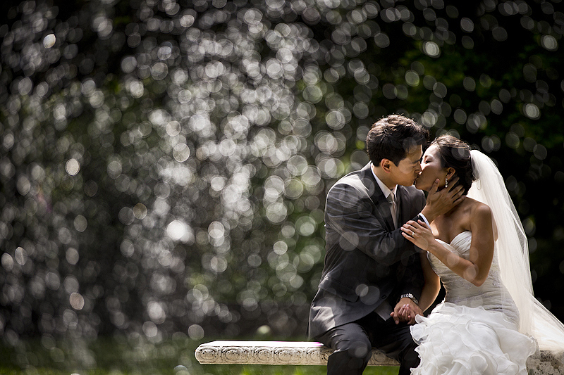Bride and groom kissing through fountain at Strong Mansion wedding