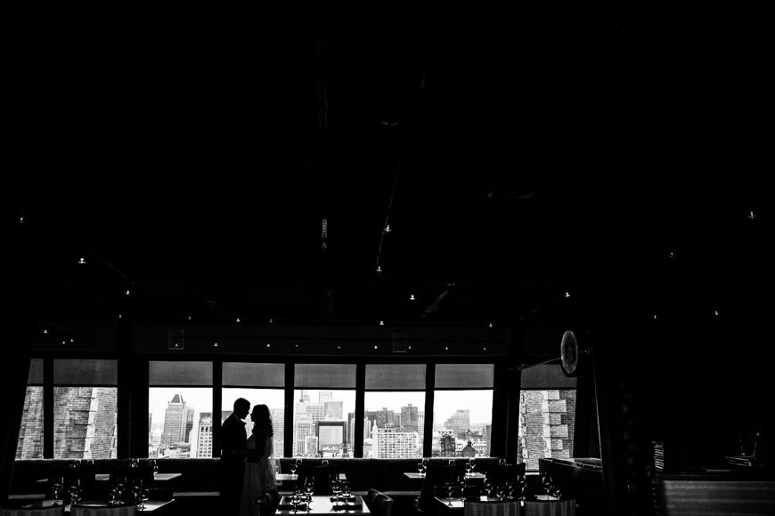 Bride and groom silhouetted against the Baltimore Skyline on the 13th floor of the Belvedere Hotel
