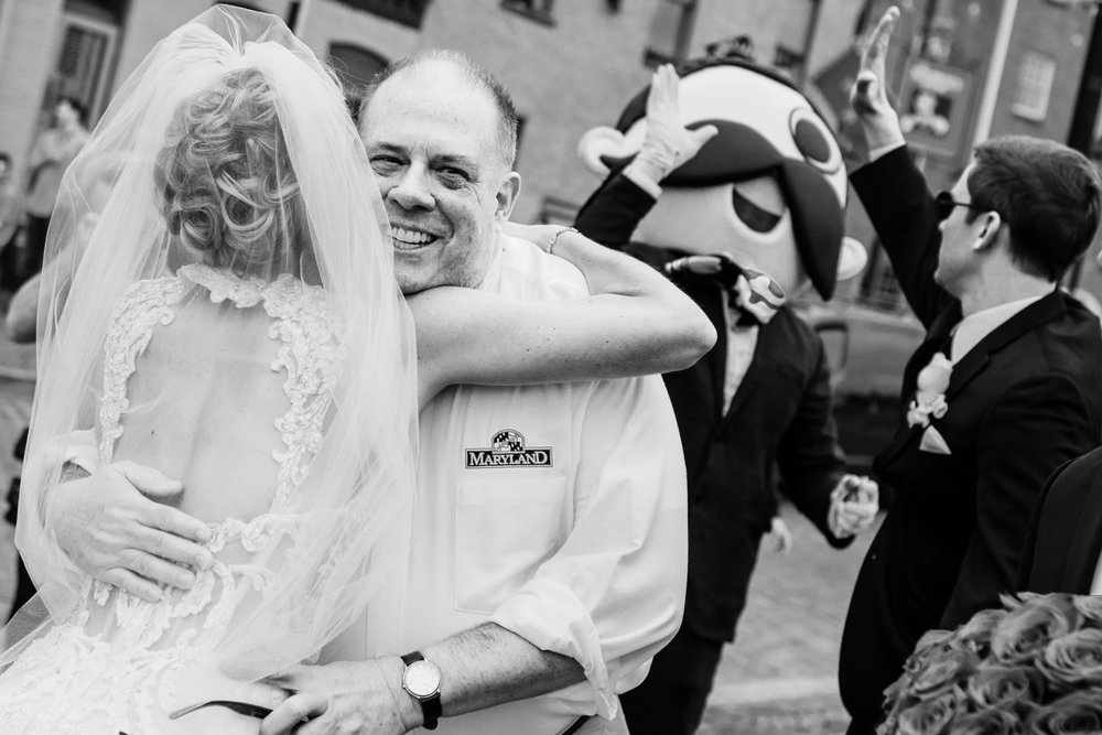 Bride hugging Maryland Governor Hogan with Groom giving a high-five to Natty Boh in the background