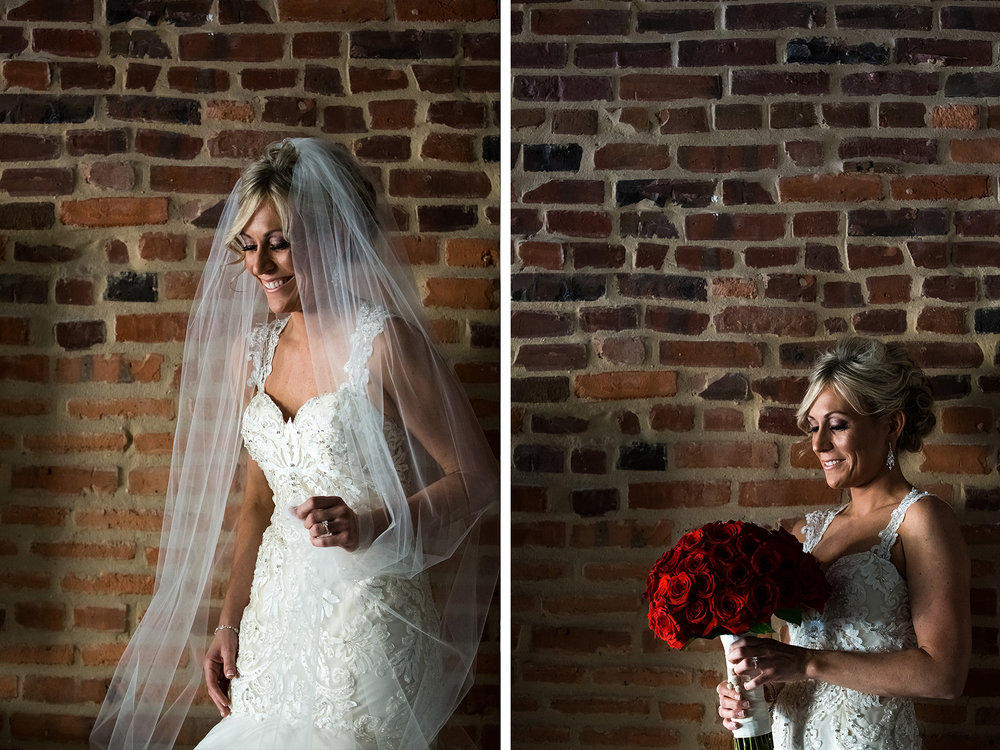 Bride holding a red rose bouquet in front of a brick wall on her wedding day in Baltimore