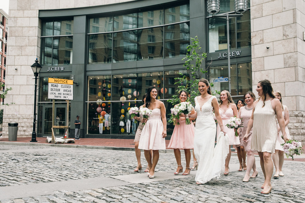 Bridal party in light pink dresses walking across the street in Harbor East, Baltimore during wedding photography session