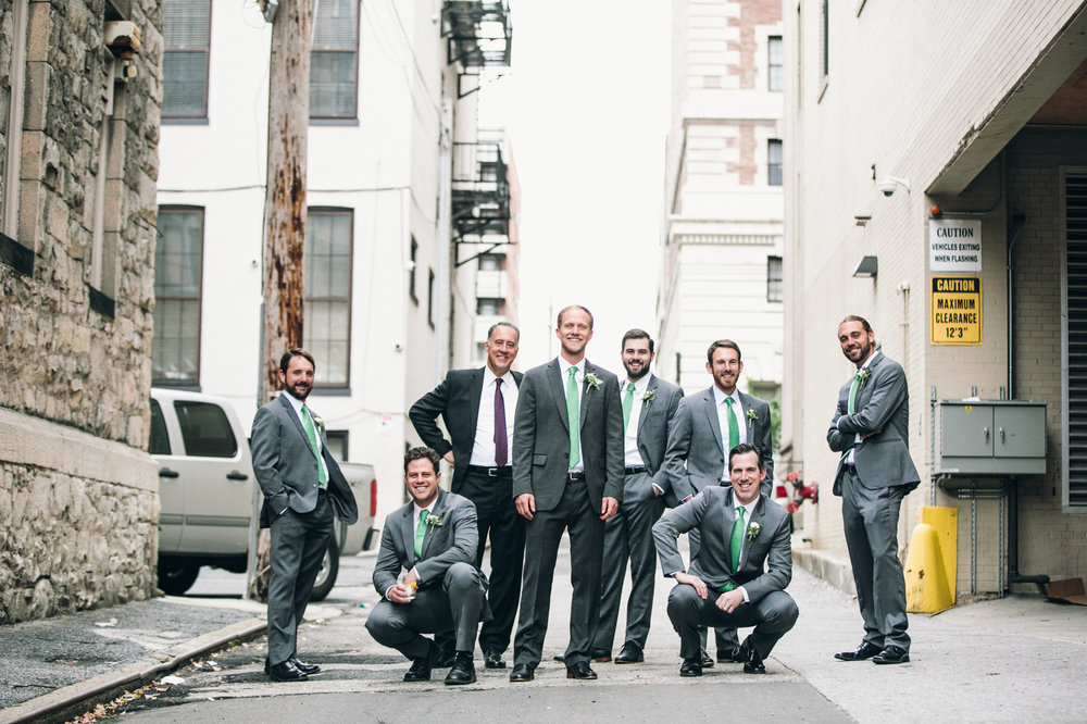 Groomsmen crouching in alley during wedding photography session in Baltimore Maryland
