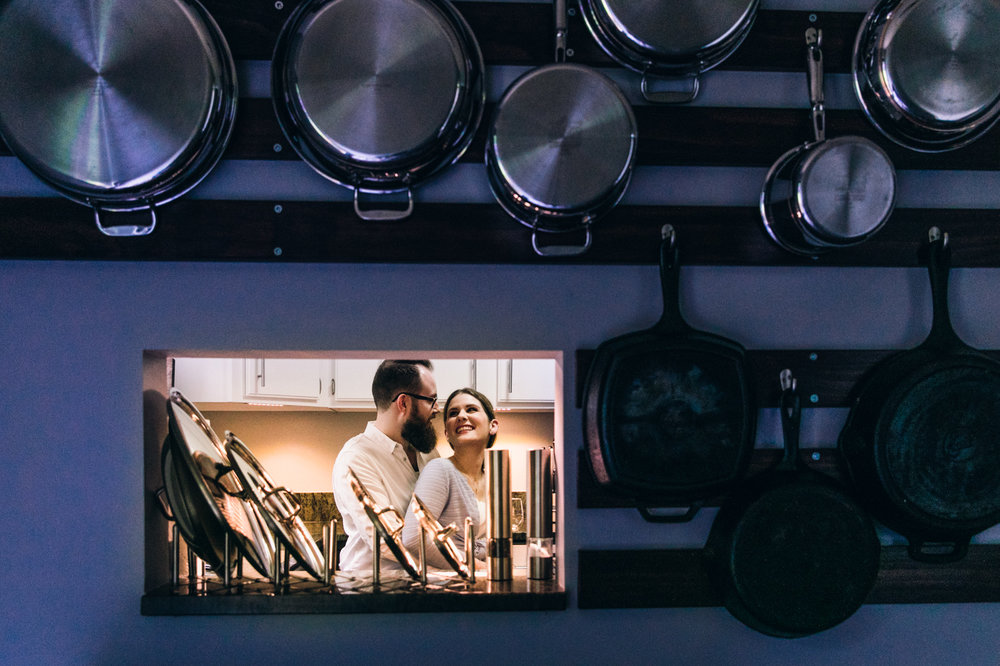 Couple hugging in their kitchen behind a wall of pots