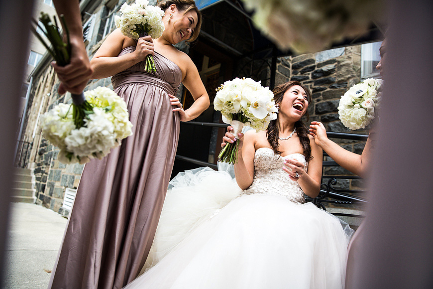 Bride laughing with her bridesmaids as they hold beautiful white bouquets.