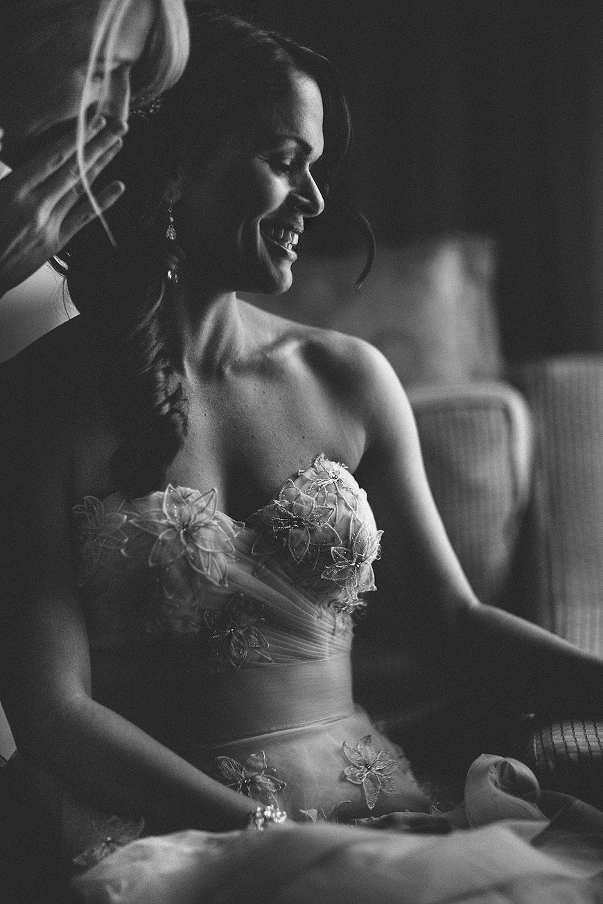 Bride laughing while someone whispers something into her ear