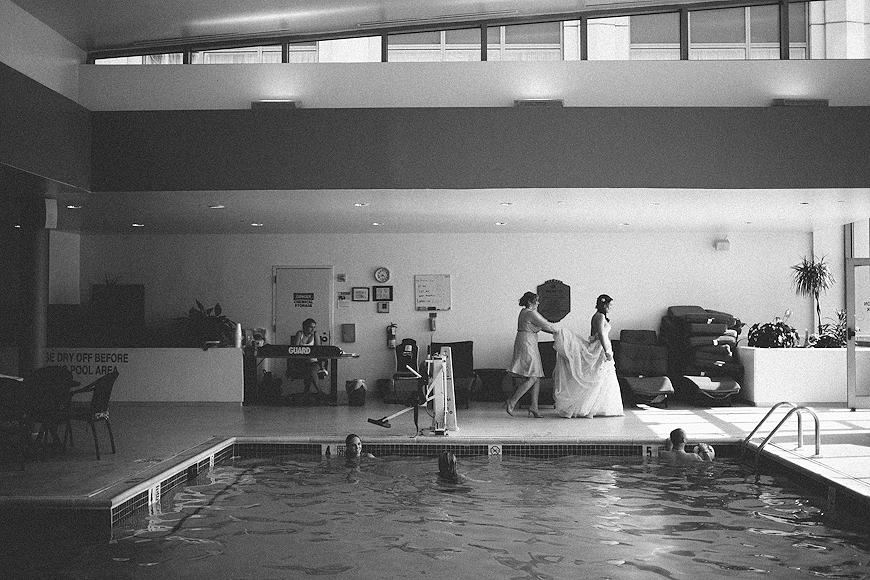 Bride walking past an indoor pool full of swimmers