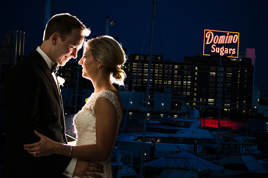Bride and groom on their wedding day in Baltimore at night in front of the neon Domino Sugars sign