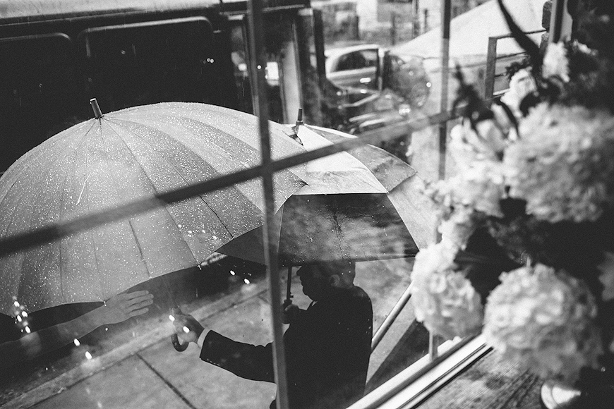 Reaching for an umbrella during a rainy day for a wedding at Woodberry Kitchen, Baltimore, MD