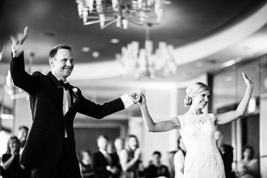 Bride and groom waving to guests as they enter the reception at their Baltimore Four Seasons wedding