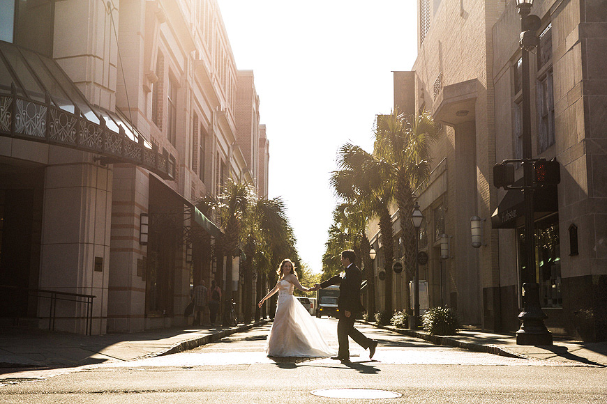 Bride and groom crossing the street in historic Charleston, SC