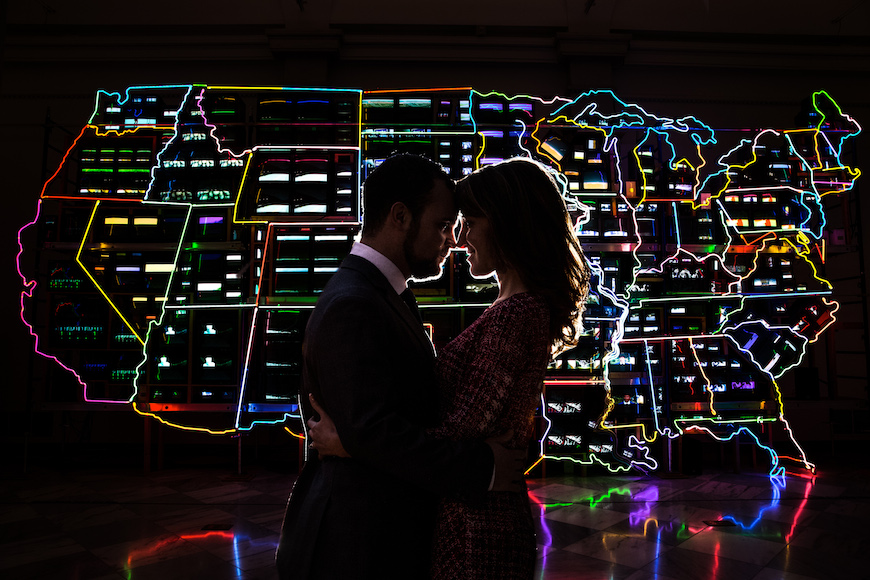 Couple posing in front of illuminated map of the US during engagement session at the National Portrait Gallery in Washington DC