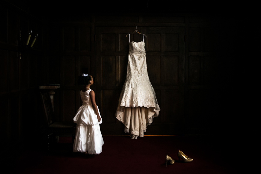 Young girl looking up to admire a wedding dress hanging in a paneled room in Nashville
